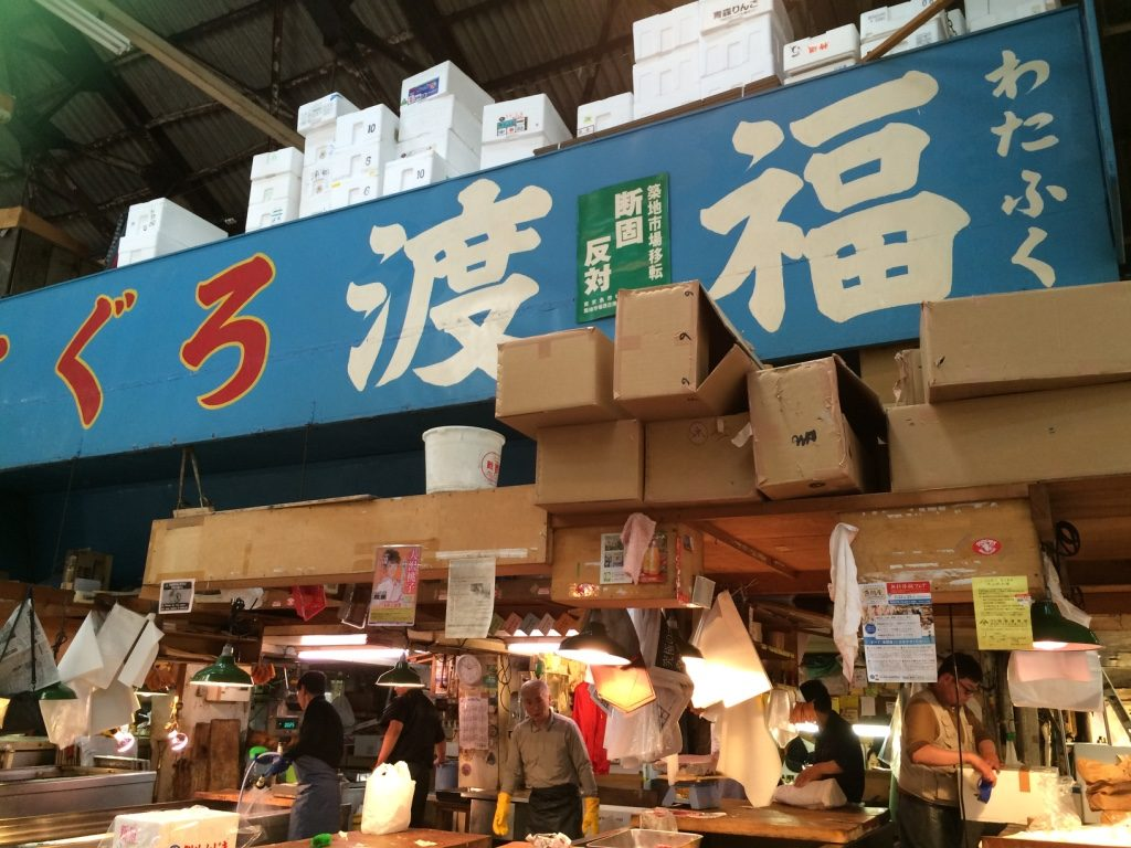 The sign in green is apparently the vendors sign against moving out of the Tsukiji Market