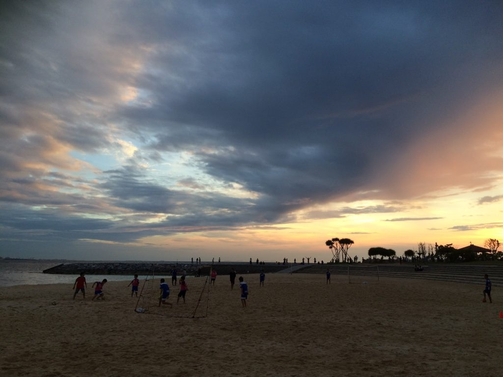 School children playing soccer as the sun was setting