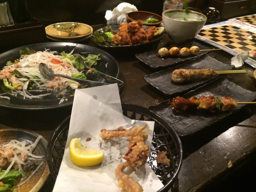 Salad, half eaten fried squid leg dish, assorted yakitori and chicken karaage