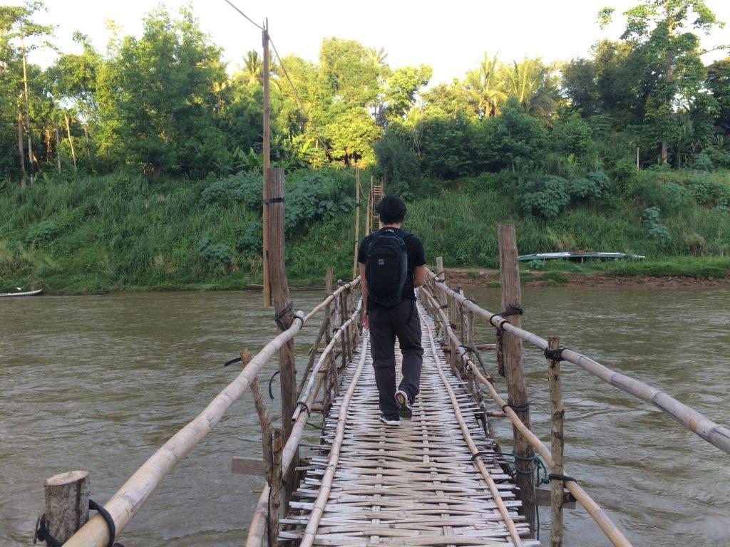 Tim crossing the bamboo bridge
