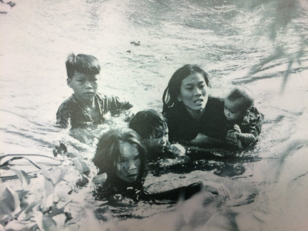 Picture by Kyoichi Sawada of a Vietnamese Mom wading across a river with her children to escape bombs from a U.S. air strike
