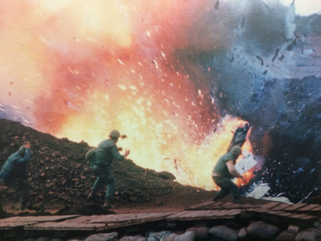 Picture by Robert J. Ellison. Ammunition dump struck by a shell fired from a North Vietnamese position explodes infront of U.S. Marines
