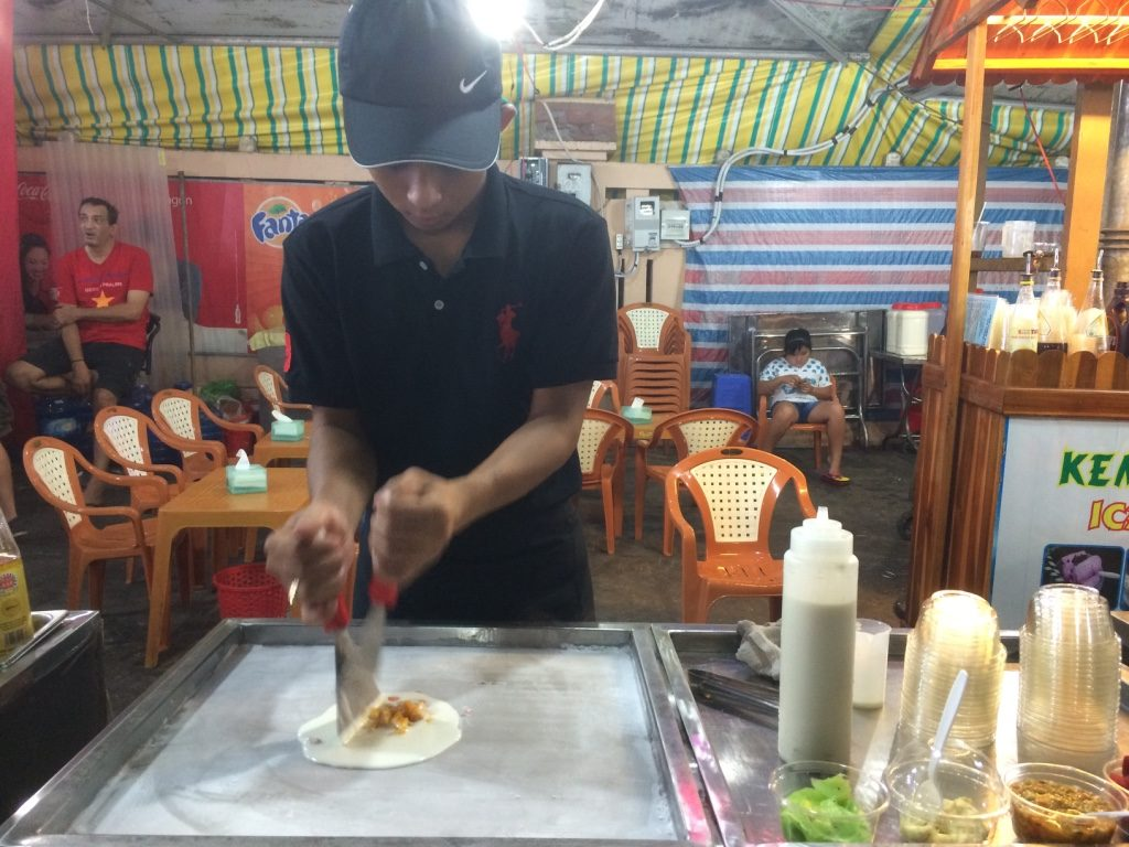 Thai rolled mango ice cream. He minces up mango and pours liquid milk on top and mixes it up.